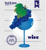Glas mit Blau, Weinrebe auf hölzernem Hintergrund Lizenzfreie Stockfotos
