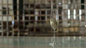 Glas mit Champagner beleuchtete durch Nachtklublichter auf Spiegelhintergrund stock footage
