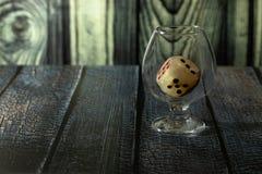 Glas mit dem Spielwürfel steht auf dem Tisch stockbild