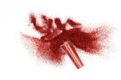 Glas mit dem verschütteten roten Funkeln magisch, himmlisches rotes Funkeln, das aus einem Glas heraus lokalisiert auf weißem Hin lizenzfreies stockbild