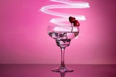 Glas mit einem Cocktail und zwei Herzen Valentinstag und Hochzeitskonzept stockbilder