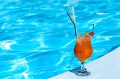 Glas mit einem Orangensaftgetränk am Rand eines blauen Pools Stockfotografie