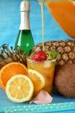 Glas mit Eis wird mit einem Orangensaftgetränk aufgefüllt, das durch Früchte umgeben wird lizenzfreie stockfotografie