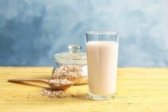 Glas mit Hafermilch und -flocken stockfotografie