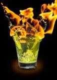 Glas mit mojito Spritzen und Feuer Stockbild
