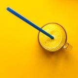 Glas mit orange frischem Saft und Stroh stockbilder