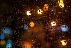 Glas mit Regentropfenhintergrund mit bokeh in der Nacht Lizenzfreie Stockbilder