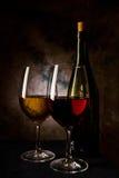 Glas mit Rot und Weißwein an der Dunkelheit lizenzfreie stockfotos