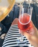 Glas mit rotem Champagner in der Hand vor dem hintergrund der Beine und des gestreiften Kleides Stockbilder