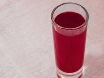 Glas mit rotem Getränkaufenthalt auf weißer Gewebetischdecke Saft, Wein oder weiches Getränkebild lizenzfreie stockfotos