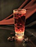 Glas mit rotem Tee auf einem Hintergrund eines Textilkaufmannes Lizenzfreies Stockbild