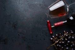 Glas mit Rotwein, Flasche mit Korkenzieher und roter Traube gruppiert sich auf schwarzem rustikalem Hintergrund, Draufsicht Platz stockbilder