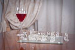 Glas mit Rotwein und Stücken auf dem Schachbrett. Satz Schach stellt auf dem spielenden Brett nahe einem Glas mit rotem Gewinn dar Lizenzfreie Stockbilder