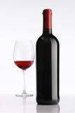 Glas mit Rotweinflasche auf weißem Hintergrund stockbilder