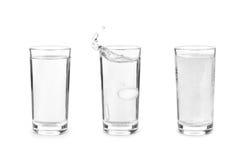 Glas mit schäumender Tablette im Wasser mit Blasen auf weißem Ba stockbild
