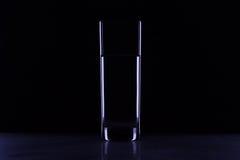 Glas mit Wasser in der Dunkelheit Stockbild