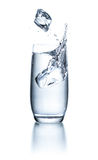 Glas mit Wasser mit Eiswürfeln und -spritzen Stockbilder