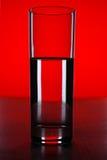 Glas mit Wasser mit rotem Hintergrund Lizenzfreies Stockfoto