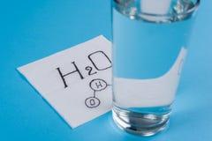 Glas mit Wasser, Serviette mit Wasserformel-Blauhintergrund Lizenzfreie Stockfotos