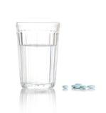 Glas mit Wasser und ein Haufen der Tabletten, Pillen Stockbild