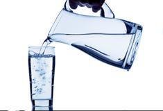 Glas mit Wasser und Krug Stockfotografie