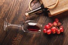 Glas mit Wein, einer Flasche und Weintraube, hölzerner Hintergrund Lizenzfreies Stockfoto