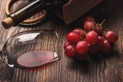 Glas mit Wein, einer Flasche und Weintraube, hölzerner Hintergrund Lizenzfreie Stockfotos