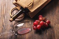 Glas mit Wein, einer Flasche und Weintraube, hölzerner Hintergrund Stockfotos