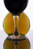 Glas mit Wein gegen eine runde Flasche Stockbild