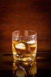 Glas mit Whisky auf Glastisch stockfotos