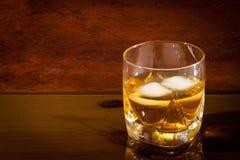 Glas mit Whisky auf Glastisch stockfotografie