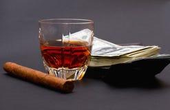 Glas mit Whisky, Zigarre und einer Reihe des Geldes nach einer braunen Geldbörse auf dem dunklen Hintergrund Lizenzfreie Stockfotos