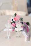 Glas mit zwei Weiß für Jungvermählten und einen Brautblumenstrauß Lizenzfreie Stockfotos