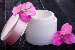 Glas natürliche Creme mit rosa Blumen lizenzfreie stockfotografie
