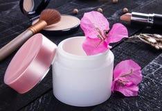 Glas natürliche Creme mit rosa Blumen lizenzfreies stockbild