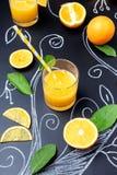 Glas Orangensaft auf dunklem Hintergrund mit gemalten Niederlassungen, wirklichen orange Blättern und Scheiben der Frucht, vertik stockfoto