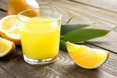 Glas Orangensaft und Orangen Lizenzfreie Stockbilder