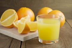 Glas Orangensaft und Orangen auf dem Holztisch Stockfoto