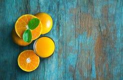 Glas Orangensaft von oben genanntem auf blauem Schmutzweinlese-Holzvorsprung Stockfotografie