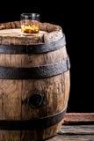 Glas oude brandewijn of whisky op de rotsen en het oude eiken vat stock fotografie