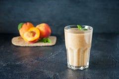 Glas perzikfruit smoothie met muntbladeren en ingridients op de donkere achtergrond Gezond, vegetarisch, het voedsel van het vega Royalty-vrije Stock Foto's