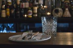 Glas, Platte, Gabel und Messer in einem restaurante, Stange im Hintergrund lizenzfreies stockfoto