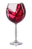 Glas rode die wijn met plons en dalingen op wijnglas op witte achtergrond wordt geïsoleerd Stock Foto