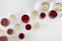 Glas rode en witte wijnen op lichte hoogste mening als achtergrond Stock Foto