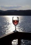 Glas rode wijn bij meer Stock Afbeelding