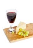 Glas rode wijn, kaas, druif die op wit wordt geïsoleerd Stock Fotografie