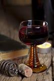 Glas rode wijn met kaars stock fotografie