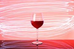 Glas rode wijn op neongloed stock foto
