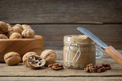 Glas rohe organische Walnussbutter und frische Nüsse auf Tabelle Kopieren Sie Raum für Text lizenzfreie stockfotos