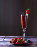 Glas rosa Champagner und Erdbeeren auf einem Holztisch Stockfotos